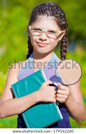Girl with magnifying glass and book  - stock photo