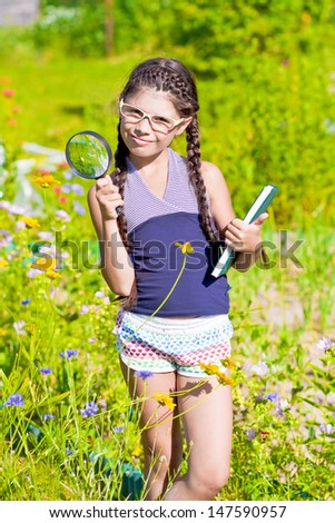 Girl with magnifying glass and book stays among flowers
