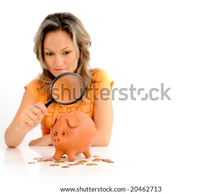 girl with magnifying glass and piggy bank against white - stock photo