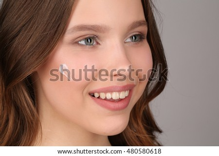 Girl with makeup and cream on her face. Close up. Gray background