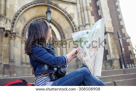 girl with map sitting on the stairs and looks at the map