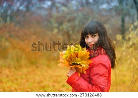 Girl with maple leaves in autumn forest - stock photo