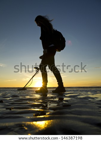 Girl with metal detector on the beach. - stock photo