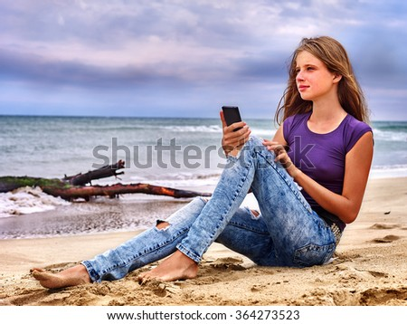 Girl with mobile phone make selfie on sand near sea.