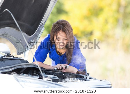 Girl with mobile phone near  broken car with open hood - stock photo