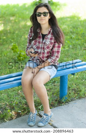 Girl with mobile phone on the street in the park.
