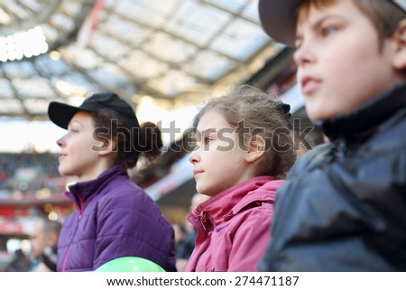 Girl with mother and brother carefully watching game at the stadium