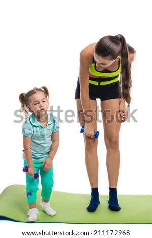Girl with mother doing gymnastic exercises with dumbbells on a white background - stock photo