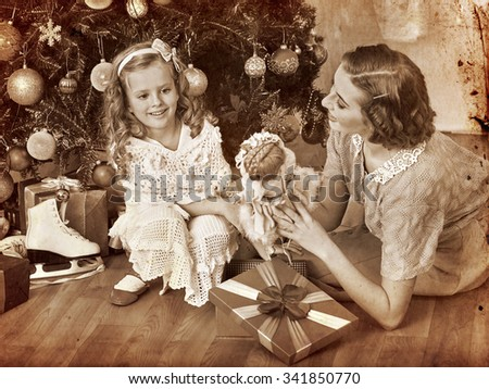 Girl with mother receiving old doll gifts lying under Christmas tree. Black and white retro vintage. - stock photo