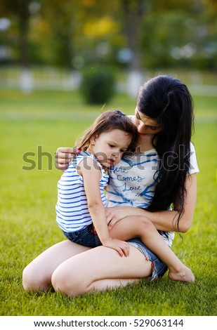 Girl with mother walking in the park, brunette