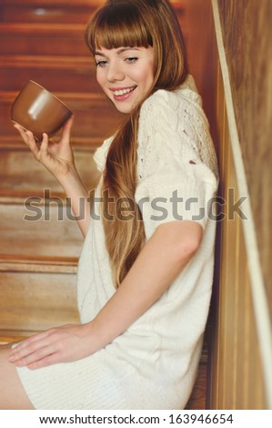 girl with mug of hot drink on the stairs - stock photo