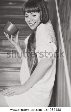 girl with mug of hot drink on the stairs
