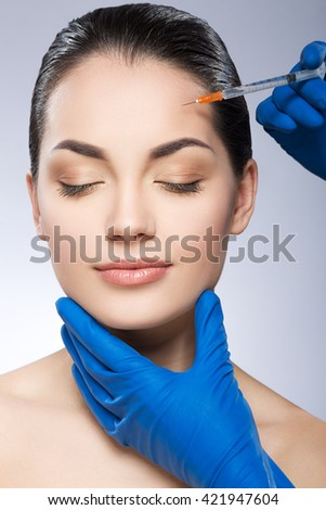 Girl with nice make-up and closed eyes. Forehead operated by plastic surgeon. Beauty injection by doctor in blue gloves. Beauty portrait, head and shoulders, full face. Indoor, studio - stock photo