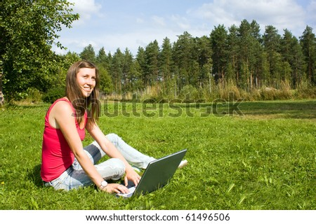 Girl with notebook on grass