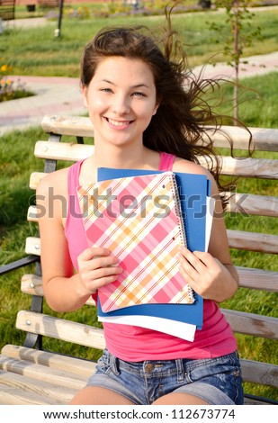 Girl with notebook sitting on the bench holding book on her chest - stock photo