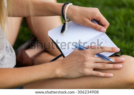 Girl with notebook writing a plan for new 2016 year - stock photo