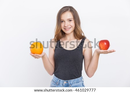 Girl with orange and apple in her hands smiling to camera. Concept of right food choices and their importance for health. Portrait. Isolated.