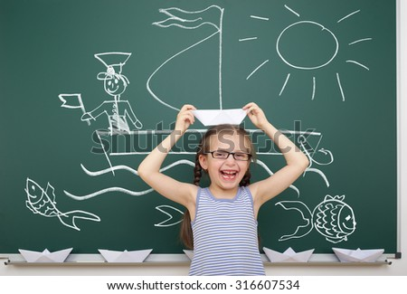girl with origami ship drawing on school board - stock photo