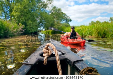 Girl with paddle and kayak on a small river in rural landscape - stock photo