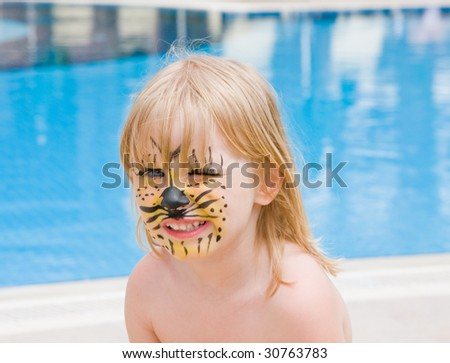 Girl with paint on his face in the pool - stock photo