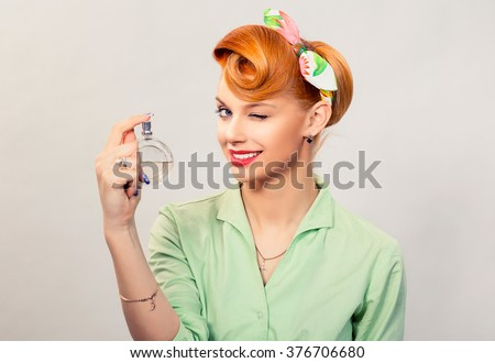 Girl with perfume. Closeup red head beautiful young woman pretty smiling pinup girl green button shirt holding bottle of perfume and smelling aroma looking at you camera, retro vintage 50's hairstyle - stock photo