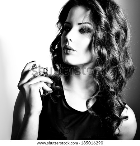 Girl with perfume, young beautiful woman holding bottle of perfume and smelling aroma. Black and white. - stock photo
