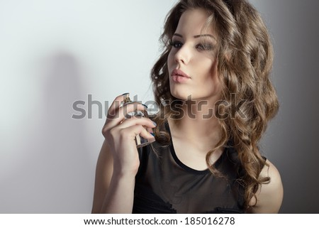 Girl with perfume, young beautiful woman holding bottle of perfume and smelling aroma, toned. - stock photo