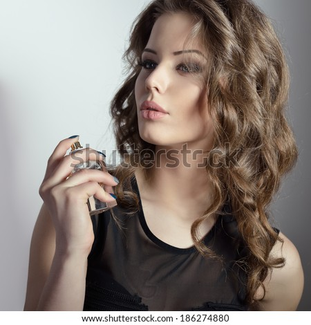 Girl with perfume, young beautiful woman holding bottle of perfume and smelling aroma. Toned. - stock photo