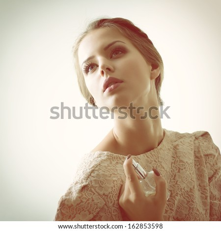 Girl with perfume, young beautiful woman holding bottle of perfume and smelling aroma, toned soft beige - stock photo