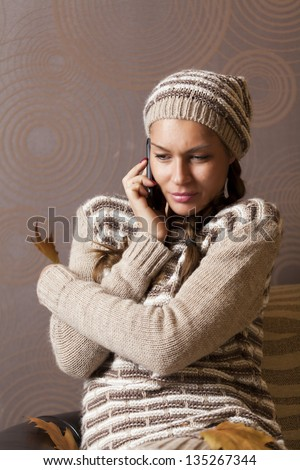 Girl with phone and sweater and cap