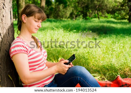 girl with phone on the grass
