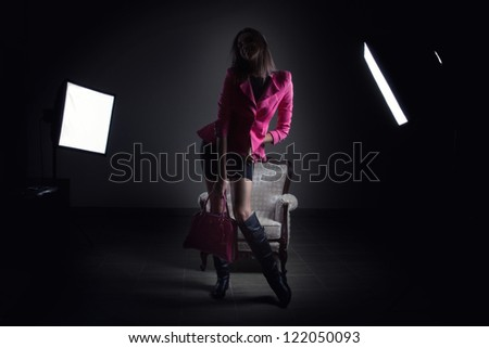 Girl with pink jacket posing in front of studio lights