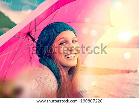 girl with pink umbrella in sunset beside a lake - stock photo