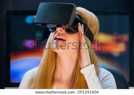 Girl with pleasure uses head-mounted display - stock photo