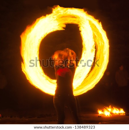 Girl with poi performs fire circle. Fireshow