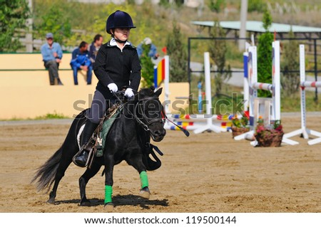 Girl with pony in jumping show - stock photo