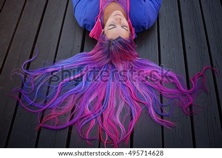 girl with purple hair, lying on the wooden floor.