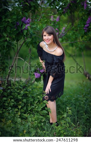 girl with purple lilacs in the spring in the park. - stock photo