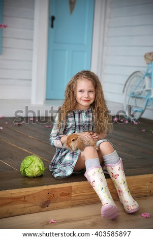 Girl with rabbit sitting on the wooden floor near cabbage in front of a house
