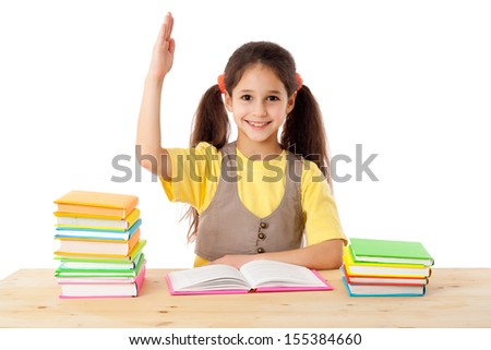 Girl with raised up hand on the table with books, isolated on white - stock photo