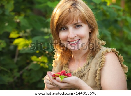 girl with raspberry in hands - stock photo