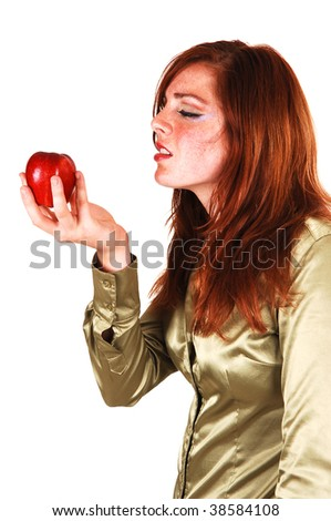 Girl with red apple, long bright red hair in a close-up shoot and can not  wait to eat the apple.