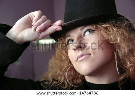 girl with red curly hairs in hat of pose in studio