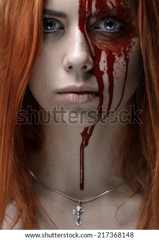 Girl with red hair, bloody face, a chain with a cross, blue eyes, vampire, murderer, psycho, halloween theme, studio shot, bloody woman - stock photo