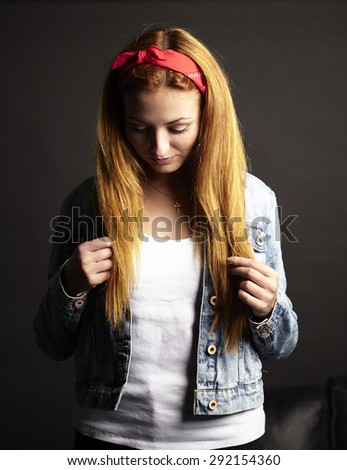 Girl with red hair in jean jacket on black background - stock photo