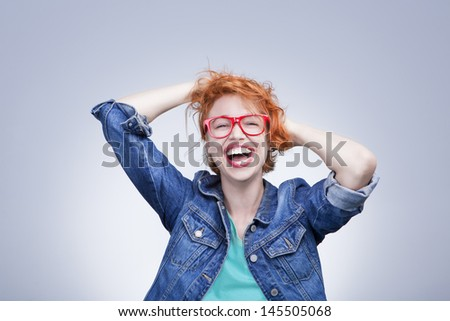 girl with red hair laughing holding his head. Tangled hair. positive emotions. Studio shot. Gray background - stock photo