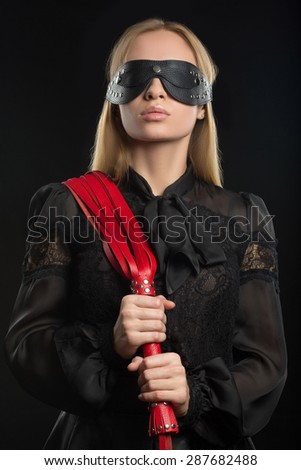 girl with red leather whip and mask BDSM - stock photo