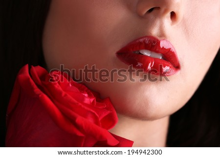Girl with red lips and rose on dark background