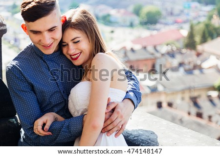 Girl with red lips leans to her boyfriend tender while posing on the roof