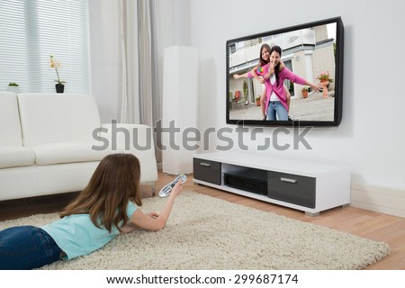 Girl With Remote Control Watching Movie On Television In Living Room - stock photo